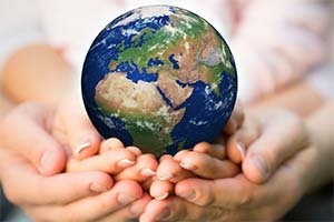 2 hands holding a globe and a green tree to show responsibility